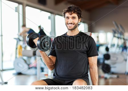 Man lifting a weight in a fitness club