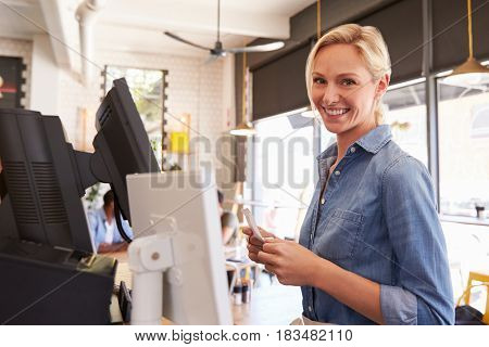Portrait Of Waitress At Cash Register In Coffee Shop