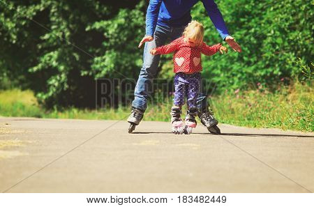 father teaching little daugther to roller skate, family sport