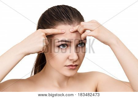 Young girl squeezes pimple on her forehead over isolated on white background.