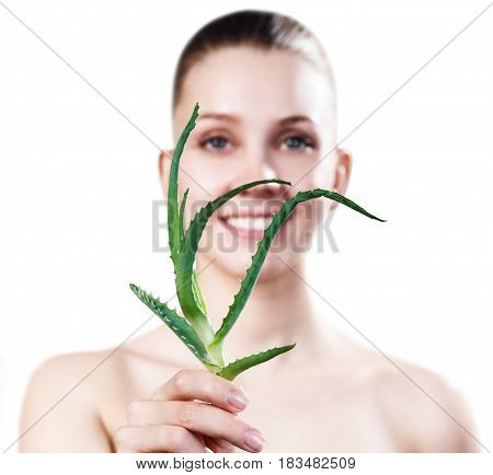 Beautiful young woman with clear skin holding Green Aloe Leaves.