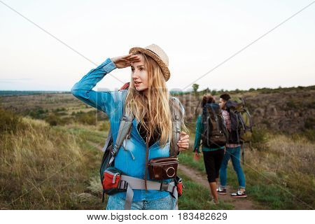 Beautiful blonde girl in hat with backpsck smiling, looking into distance, friends tourists background. Copy space.