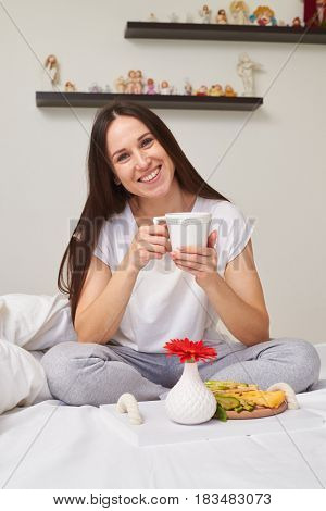 Mid shot of smiling woman in pajamas drinking tea and enjoying romantic breakfast sitting in the bed