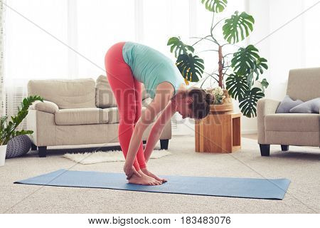 Wide shot of skinny female stretching on yoga mate in living room