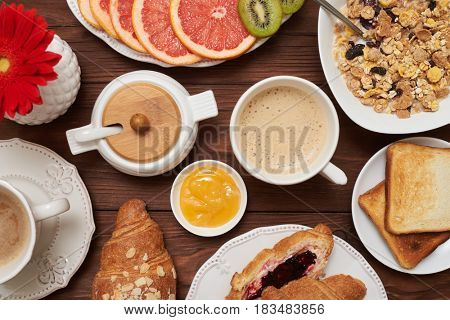 Flat lay picture of confectionery with coffee and jams. French croissants sprinkled with almonds, cup of coffee and fruits, and corn flakes