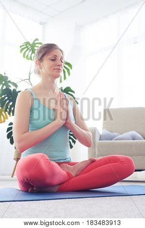 Low angle of relaxed girl in sportswear meditating while sitting on yoga mat