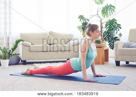 Wide shot of sportive relaxed woman doing upward-facing dog pose