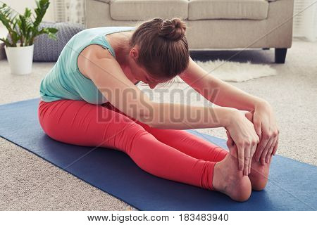 Close up of charming sportswoman practicing yoga in seated forward bend pose