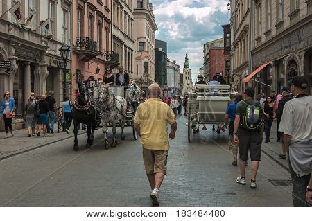 KRAKOW, LESSER POLAND / POLAND - NOVEMBER, 2014: Horses, tourists and locals on the street of the royal city