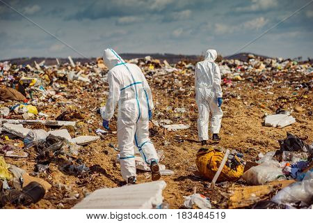 Two scientists in coveralls working in landfill.