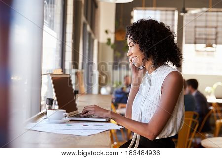 Businesswoman Using Phone Whilst Working In Coffee Shop