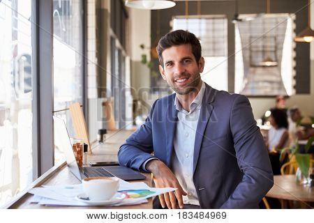 Portrait Of Businessman With Laptop Working In Coffee Shop