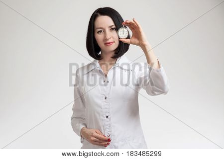 the beautiful woman the doctor with a stop watch on a white background