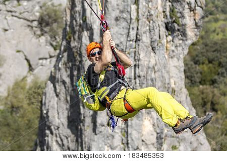 Young male climber hanging on rope and smiling at camera on background of rock