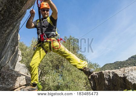 Young male alpinist hanging on rock and smiling at camera