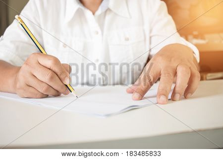 student holding pencil writing test in exercise exams answer sheets in classroom educational school