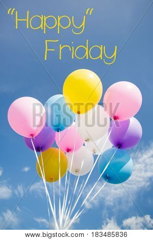 Happy Friday word on colorful party balloon floating in mid air against a bright blue sky.