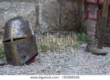 Helmet of a medieval knight on the ground, in the background feet with ancient footwear