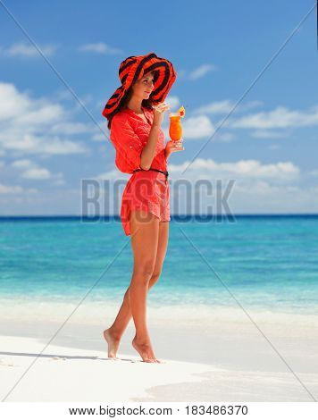 Fashion woman drinking cocktail on the beach. Happy island lifestyle. White sand, blue cloudy sky and crystal sea of tropical beach. Vacation at Paradise. Ocean beach relax, travel to Maldives islands