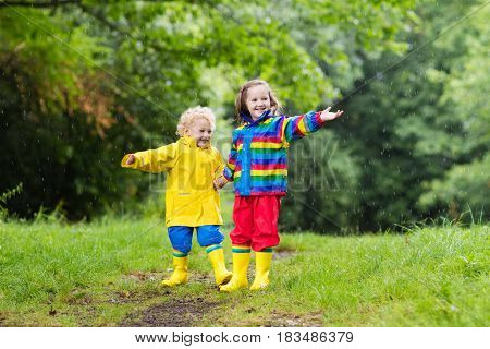 Kids Play In Rain And Puddle In Autumn