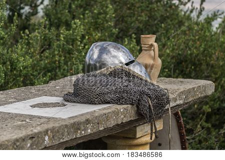 Helmet, chainmail, sword and shields on a stone table of a medieval armor knight ready for battle