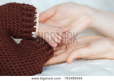 Newborn baby's feet on mom hands. On the background of a brigh.