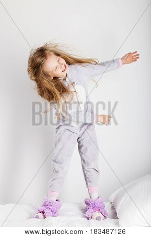 Funny Little Girl In Pajamas Jumping And Having Fun In Bed At Home.