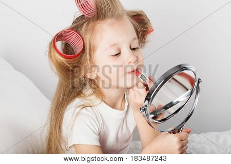 Beautiful Little Lady With Curlers On Her Head Looking At Mirror And Paints Lips. Fashion Baby Girl