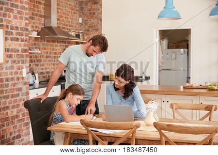 Parents Helping Daughter With Homework At Kitchen Table