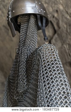 Helmet, chainmail, sword and shields of a medieval armor knight ready for battle