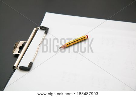 Clipboard with paper and pencil on a white table.