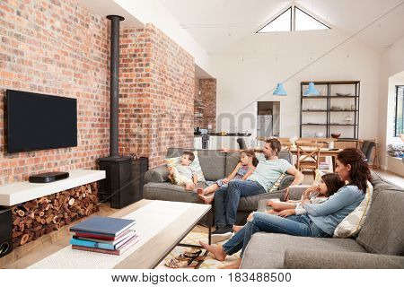Family Sit On Sofa In Open Plan Lounge Watching Television