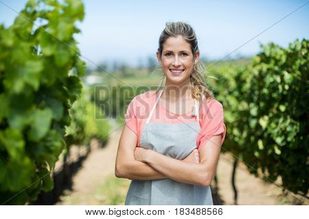 Portrait of smiling female farmer with arms crossed standing at vineyard