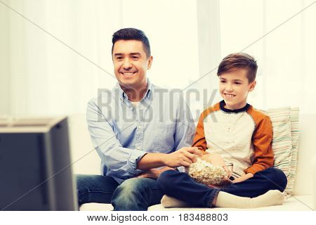 family, people, technology, television and entertainment concept - happy father and son with popcorn watching tv at home