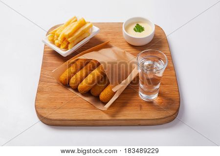 Fish Sticks On A Wooden Board With Sauce And Fried Potatoes