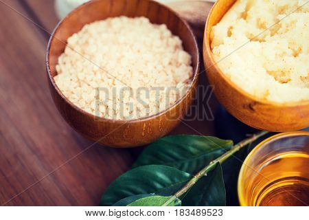 beauty, spa, body care, natural cosmetics and and wellness concept - close up of himalayan pink salt and body scrub with leaves on wooden table