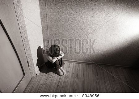 Child sitting in a room corner