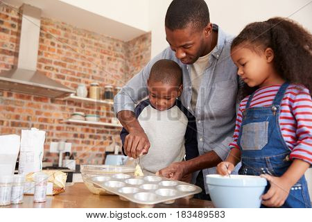 Father And Children Baking Cakes In Kitchen Together