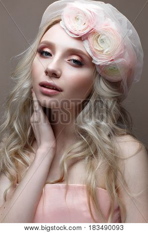 Young girl with curls in a hat with veil. Beautiful model with a wreath of flowers on her head. A gentle summer image. Beauty of the face.