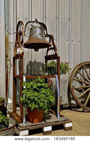 An old school bell attached to a frame, wooden buggy wheel, and plants serves as decoration.