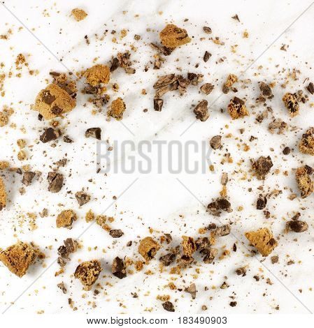 A square photo of a frame made up by chocolate chips cookie crumbs, shot from above on a white marble background, with a place for text