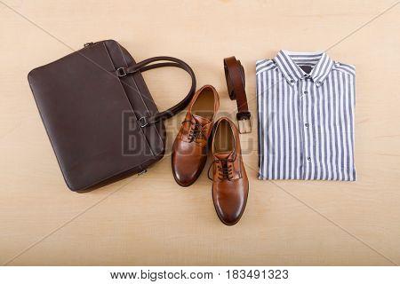 Mans shoes and shirt ,belt, bag on wood background