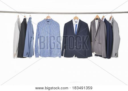 Set of different suits Shirts with ties on wooden hangers