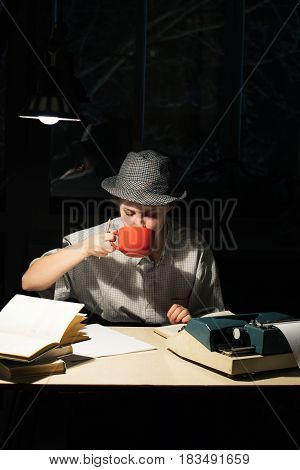 Portrait of a girl in a hat sitting at a table with a typewriter and books drinking tea at night