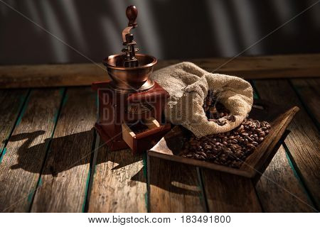 Coffee mill on dark rustic background. Wood table.