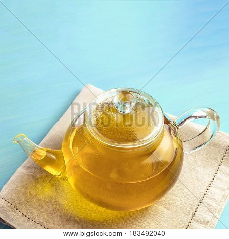 A square photo of a teapot full of tea, shot on a teal texture with a place for text