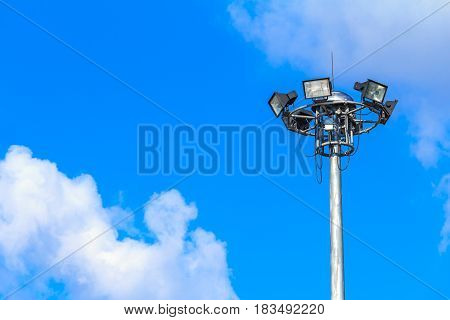 Halogen spotlights and blue sky with white clouds.