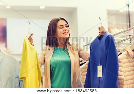 sale, clothes , shopping, fashion and people concept - happy young woman choosing between shirt and jacket at clothing store