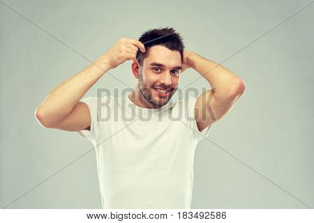 beauty, grooming and people concept - smiling young man brushing hair with comb over gray background