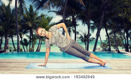 fitness, sport, people and healthy lifestyle concept - woman making yoga in side plank pose on mat over hotel resort pool on tropical beach background